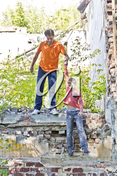 Father and teenager son are playing in ruins