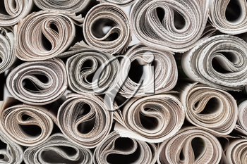 Stack of newspapers rolls, texture background.