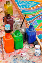 paintbrushes, bottles with color pigments and ornament on silk