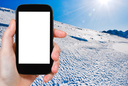 travel concept - tourist photograph blue cold snow on Alps mountain in Portes du Soleil region, Morzine - Avoriaz, France on tablet pc with cut out screen with blank place for advertising logo