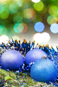 Xmas still life - blue balls, tinsel at green tree with blurred green and blue Christmas lights background