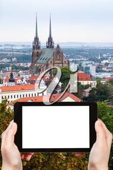 travel concept - tourist photographs Brno city with Cathedral of St Peter and Paulon on tablet pc with cut out screen with blank place for advertising logo