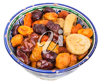 Central Asian dried fruits in traditional ceramic bowl isolated on white background