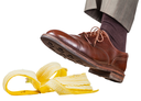 male foot in the left brown shoe slips on a banana peel isolated on white background