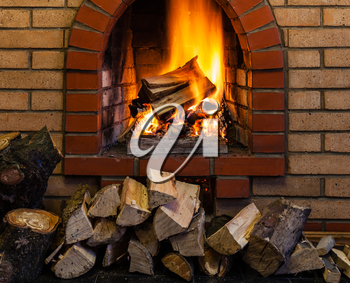 stack of wood and burning wood in indoor brick fireplace in country cottage