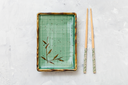 top view of green plate and chopsticks on gray concrete board