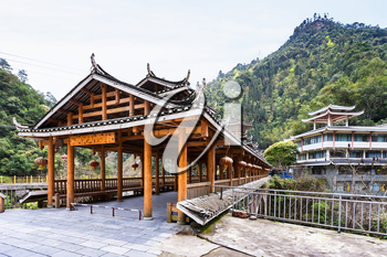 travel to China - entrace to Dong people style bridge in Jiangdi village over river in Longsheng Hot Springs National Forest Park of Xiangshan District in spring season