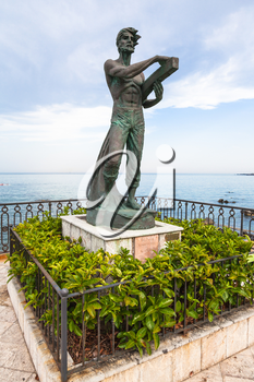 GIARDINI NAXOS, ITALY - JUNE 28, 2017: sculpture L' Uomo e il Mare (Man and the Sea) on waterfront in Giardini-Naxos town. Giardini Naxos is seaside resort on Ionian Sea coast since the 1970s