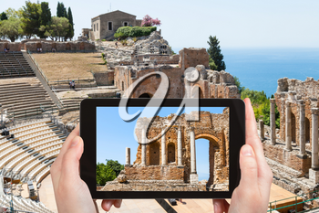 travel concept - tourist photographs Teatro antico di Taormina, ancient Greek Theater (Teatro Greco) in Taormina city in Sicily Italy in summer on tablet