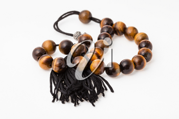 tangled worry beads from tiger's eye gemstones on white paper background
