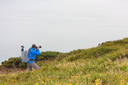 Male photographer wearing professional gear is taking photos on a cliff