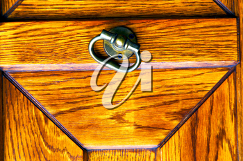 lombardy  castellanza blur   abstract   rusty brass brown knocker in a  door curch  closed wood italy   cross