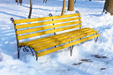 Yellow wooden bench among the snowbanks in winter park on a sunny fine day