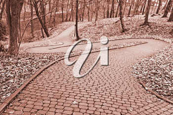 Park paved walkway that runs steeply down, early spring evening in Lviv, Ukraine, toned photo