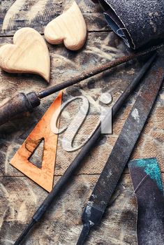 Symbolic wooden hearts cut by hand and carpenter tools