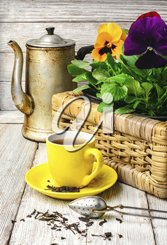 Yellow porcelain cup with tea and basket of decorative Pansy