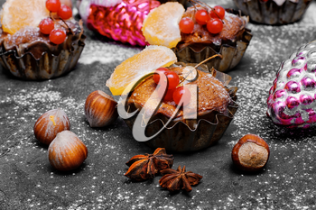few Christmas cupcakes with fruits on black background