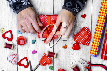 Packing holiday gifts for Valentine's day.Thread,button and symbolic heart.