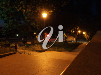 Night scene of the city. Bright street lights and staircase of granite stone under green trees at the evening street