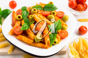Plate of penne pasta decorated with cherry tomatoes, olives and herbs on a wooden tray