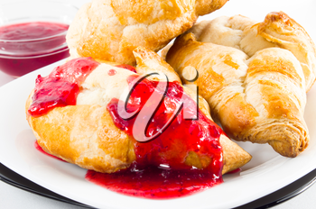 Several croissants with strawberry jam on white plate closeup