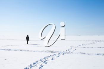 Footsteps of lonely girl walking on frozen sea covered with snow. Russian winter