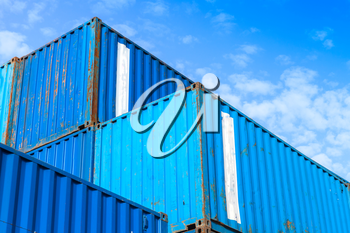 Blue metal Industrial cargo containers are stacked in the storage area under blue cloudy sky