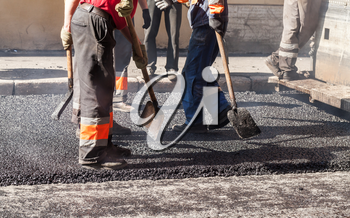 Urban road is under construction, asphalting in progress, group of workers in uniform with shovels