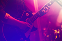 Electric guitar player on a stage with colorful blue and purple scenic illumination, soft selective focus