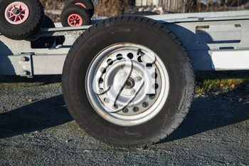 Closeup photo of trailer wheel on gray asphalt road