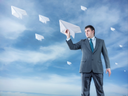 Businessman with big paper plane and isolated on sky background