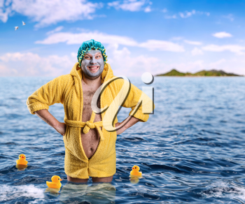 Crazy man with face pack stands in water