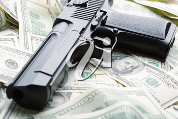 Heap of $100 dollar bills and handgun