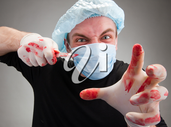 Mad mental sick blood soiled surgeon with knife