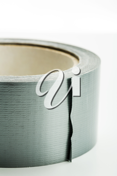 Closeup of a roll of silver adhesive tape on white background