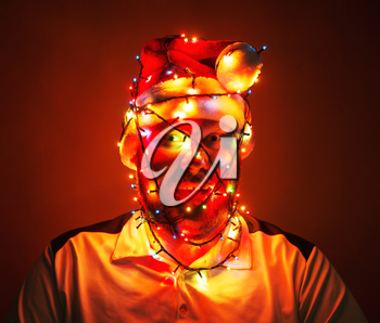 Man wrapped in xmas lights sitting in the dark