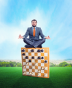 Businessman meditating sitting on the chess board edge