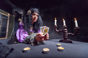 Sorceress working with cards in her room, candles on the table