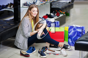 Young woman sitting on the floor in the shoe store choosing shoes