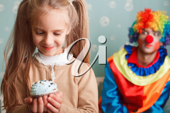 Smiling little girl holds cake in hand and makes a wish. Funny clown on the background.