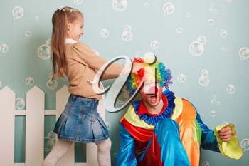 Little girl pulls clown hair. White fence decoration on the background.