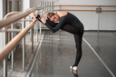Skill ballet dancer posing in class, barrre and white wall on background