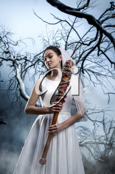 Beautiful bride with bloody baseball bat against the background of the dried tree