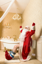 Joyful Santa Claus with his pants down sitting on the toilet. Christmas humor