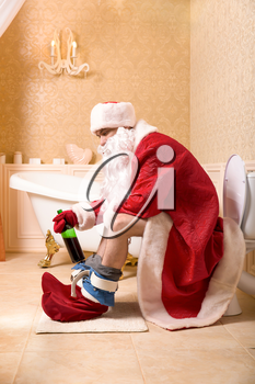 Funny drunk Father Christmas with bottle of alcohol sitting on the toilet.