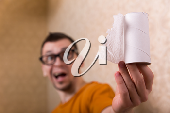 Surprised man in glasses sitting on the toilet bowl, out of paper