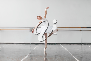 Beautiful female ballet dancer keep the rack in ballet class, barre and white wall on background