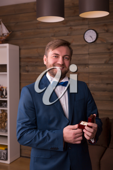 Happy groom in suit and bow-tie holding wedding ring in his hand, wooden room interior on background