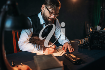 Bearded journalistr in glasses writes with a feather. Retro typewriter, books and vintage lamp on the desk