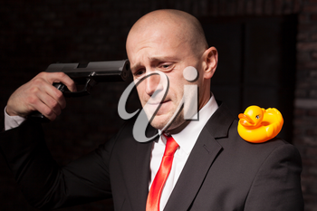 Contract murderer in suit and red tie with toy duck on shoulder aims a pistol in his head. Professional secret agent nervous breakdown concept